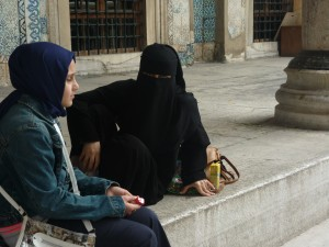 Nena con burka diante da mezquita azul